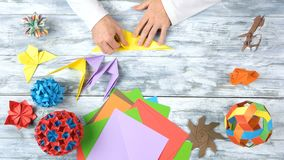 Folding colorful paper while making origami figures. Torning yellow paper by hands. Folding colorful paper while making origami figures. Top view, flat lay royalty free stock photos