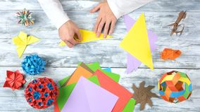 Torning yellow paper by hands. Folding colorful paper while making origami figures. Top view, flat lay royalty free stock image