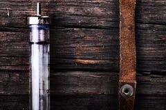 Torniquete da seringa e da camurça na superfície de madeira áspera como um co Foto de Stock