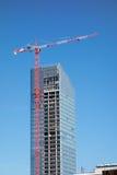 Tornkran överst av konstruktionsskyskrapan som bygger över blå himmel Royaltyfria Bilder