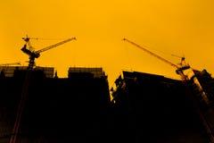 Tornkran på en konstruktionsplats på soluppgång arkivfoton