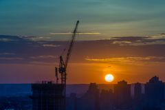 Tornkran på en konstruktionsplats på soluppgång royaltyfri bild