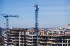 Tornkranar mot den blåa himlen konstruktionshus under Arkivbild