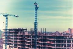 Tornkranar mot den blåa himlen konstruktionshus under Royaltyfri Bild