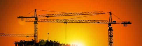 Tornkranar och byggnadskontur med arbetare på soluppgång Arkivfoton