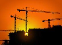 Tornkranar och byggnadskontur med arbetare på soluppgång Royaltyfri Fotografi