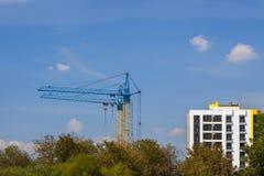 Tornkranar på en konstruktionsplats nära byggnad och gräsplanträd Arkivfoton