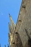 Tornspiror och vattenkastare på stenväggen av kyrkan i Barcelona Royaltyfri Bild