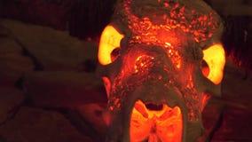 Toro del cranio con i corni e la luce rossa dall'interno dell'attaccatura sulla parete di pietra per interior design Trofeo di ca video d archivio