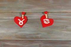 Toro e cancro segni dello zodiaco e del cuore feltro B di legno fotografia stock