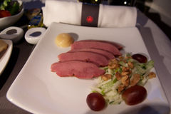 TORONTO, CANADÁ - 28 de janeiro de 2017: Refeição de bordo da classe executiva de Air Canada, jantar com o peito de pato fumado d Imagens de Stock