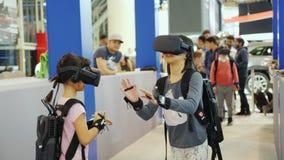 Toronto, Canadá, o 20 de fevereiro de 2018: Jogo de duas meninas nos capacetes da realidade virtual Sensores nas mãos e na sacola filme