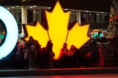 TORONTO, CANADÁ - 2018-01-01: Torontonians delante de la hoja de arce que brilla intensamente, el símbolo canadiense principal, t Imagenes de archivo