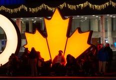 TORONTO, CANADÁ - 2018-01-01: Torontonians delante de la hoja de arce que brilla intensamente, el símbolo canadiense principal, t Fotografía de archivo libre de regalías