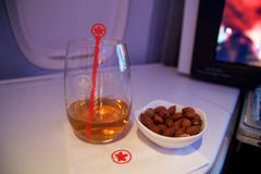TORONTO, CANADA - JAN 28th, 2017: Air Canada Business class in a passenger plane. A glass of whisky and some warm nuts Royalty Free Stock Photography
