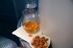 TORONTO, CANADA - JAN 28th, 2017: Air Canada Business class in a passenger plane. A glass of whisky and some warm nuts Stock Image
