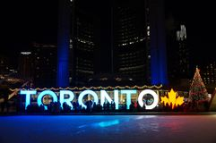 TORONTO, CANADA - 2018-01-01: People in front of TORONTO sign with Christmas tree in the night viewed across the skating
