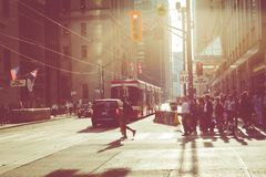 TORONTO, CANADA - SEPTEMBER 17, 2018: Rush hour at Toronto downtown, many people on the street. Sunset time with sun flares. royalty free stock images