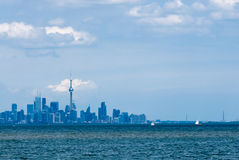 Toronto city skyline across water under clouds. Toronto city skyline from across rippled water against cloudy sky Royalty Free Stock Images