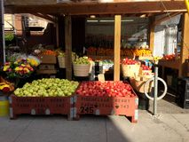 Toronto fruit market selling apples in fall. A side view of a Toronto fruit market with large containers full of apples in addition to its other wares. The Royalty Free Stock Images
