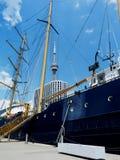 Toronto harbor with white condo and blue sailboat stock photos