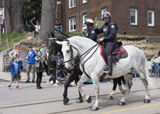 Toronto mounted police officers wave to viewers along the Queen Street East during the Beaches Easter Parade 2017 Stock Photos