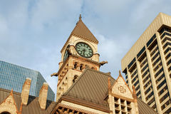 Toronto old city hall. Old city hall of toronto in neo-gothic style between modern skyscrapers under the sunset light Stock Images