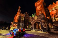 Amazing view of Casa loma old, vintage castle at inviting night time, lit with various lights and car model back to the future