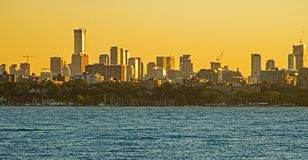 Toronto Skyline Bathed In Golden Sunrise Light. View of the downtown Toronto, Ontario, Canada skyline across Lake Ontario from Etobicoke Point in Humber Bay Park royalty free stock photo