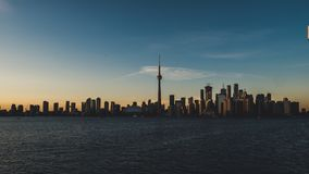 Toronto skyline during sunset seen from toronto island with lake ontario infront royalty free stock photos