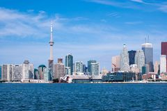 Toronto skyline under a clear sky. Daytime skyline of Toronto, taken from the shores of Lake Ontario under a blue sky with clouds royalty free stock photo