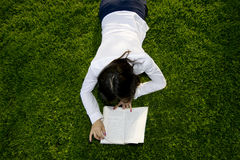 Toronto universities. Young nice attentive woman lies on green grass and reads book Royalty Free Stock Photo