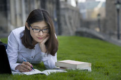 Toronto universities. Young nice attentive woman lies on green grass and reads book Royalty Free Stock Image