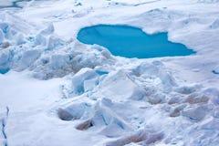 Toros vom Landursprungseis weil schmutziger und des Schlammfeld-Schnees Morast in der Entwicklung - blaue Pfütze auf mehrjährigem Lizenzfreie Stockfotografie