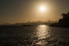 Torpedowerf en het silhouet van de binnenstad bij zonsopgang in San Francisco stock afbeelding