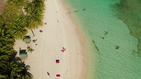 Torpical island with white sandy beach, top view. Aerial view sandy beach on tropical island with tourists palm trees and clear blue water. Philippines, Palawan stock footage