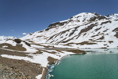 Torquoise lake in high altitude mountains with ice cakes Stock Image