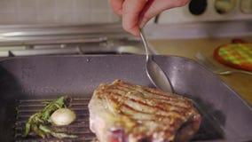 Torréfaction d'un bifteck de boeuf avec le romarin et l'ail sur une casserole noire chaude et un pétrole se renversant là-dessus  banque de vidéos