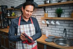 Torr disk för försiktig vuxen man i kök Han ser plattan och leende lite Bara i rum Kläderförkläde royaltyfri bild