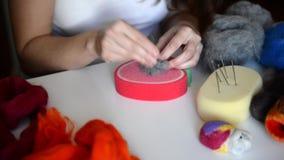 Torr felting: kvinnan fördelar fibrerna av grå filt för att ge den önskade formen Mästarklass på skapelsen av lager videofilmer
