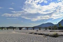 Torr flodbädd med bron, blå himmel och moln i bakgrund Arkivbild