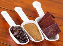 Torr kakaoböna för mörker, stycken av choklad och pudrad kakao inom av vita retro skopor på träbakgrund Arkivfoton