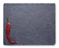 Torr röd peppar kritiserar på svart tavla arkivfoton