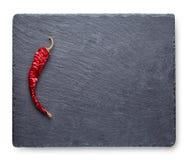 Torr röd peppar på en kritiserasvart tavla arkivbilder