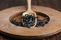 Torra gröna teblad i träsked över den bruna plattan Arkivfoton