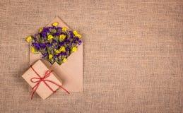 Torra lösa blommor i ett kuvert och en ask med en gåva på en naturlig linnetorkduk Mallar och texturer Fotografering för Bildbyråer