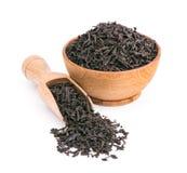 Torra sidor för svart te i en träbunke som isoleras på vit Royaltyfria Foton