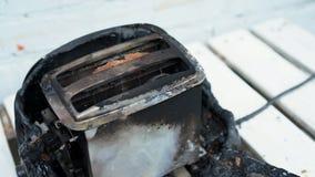 Torradeira ardente Torradeira com as duas fatias de brinde travadas no fogo sobre o fundo branco filme