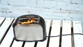 Torradeira ardente Torradeira com as duas fatias de brinde travadas no fogo sobre o fundo branco vídeos de arquivo