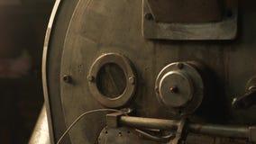 Torrador do feijão de café no trabalho em uma sala da produção filme